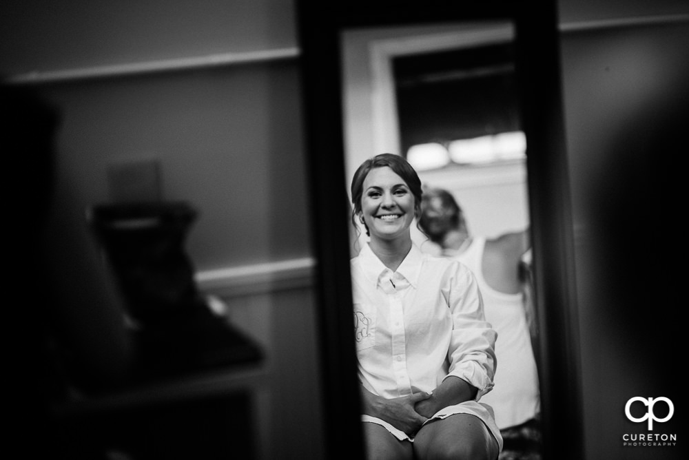 Bride looking at her makeup in the mirror.