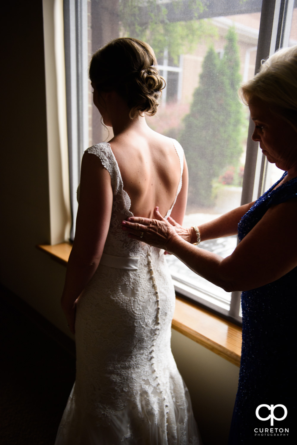 Bride's mother helping her into the dress.