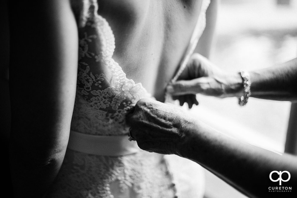 Bride's mom fastening the back of the dress.