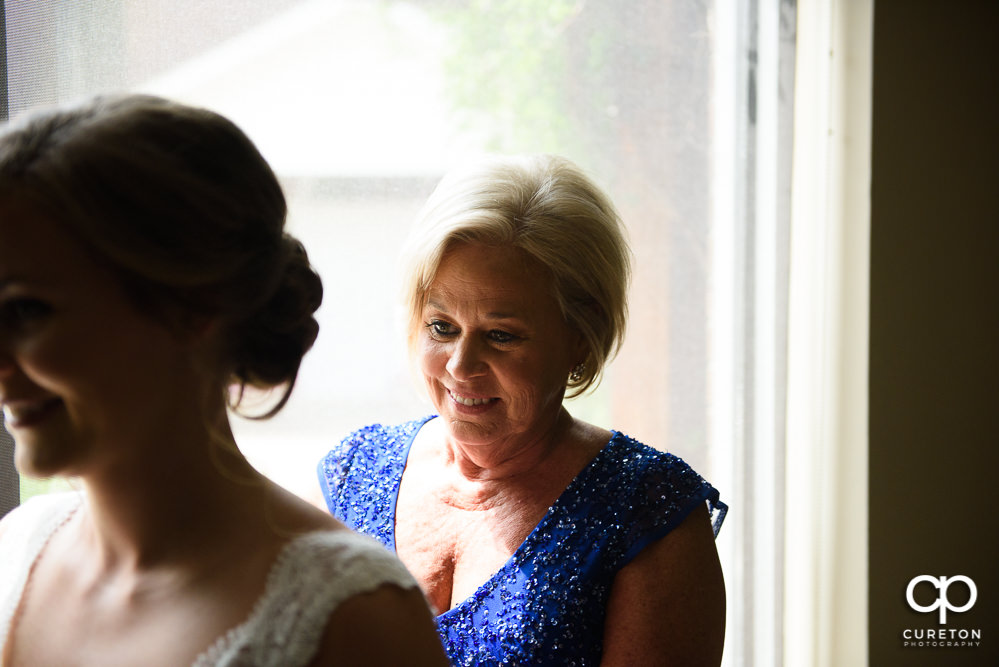 Bride's mom helping her get ready.