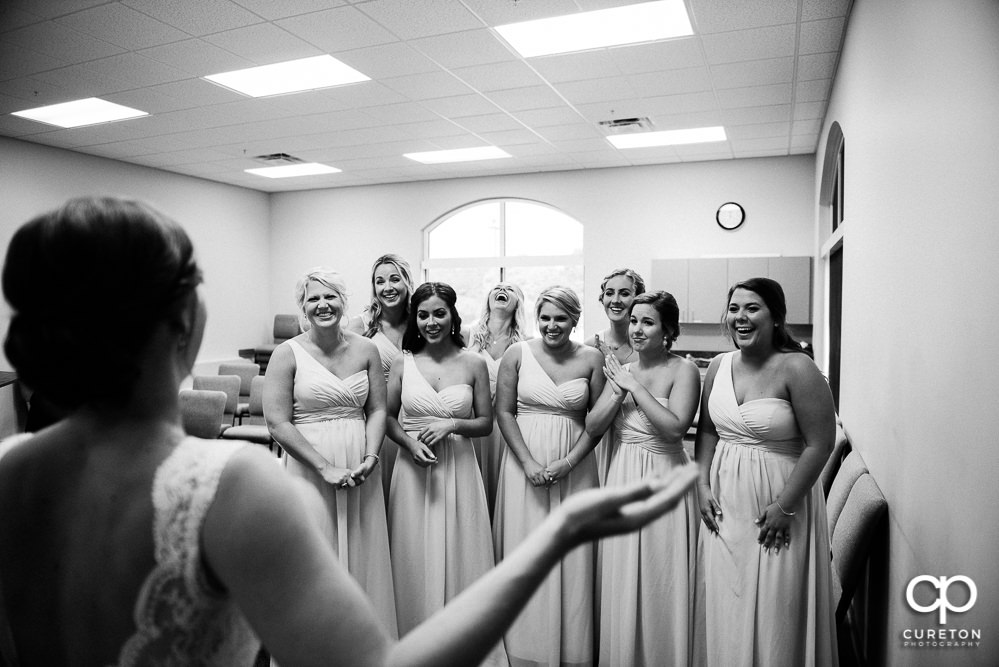 Bride revealing the dress to the bridesmaids.