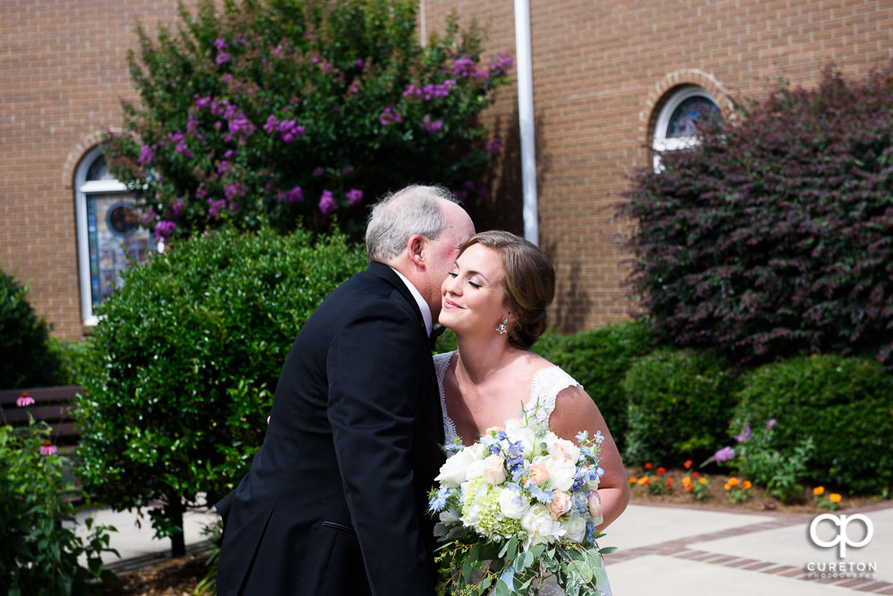 Bride having a first look with her dad in the courtyard of Covenant United Methodist Church.