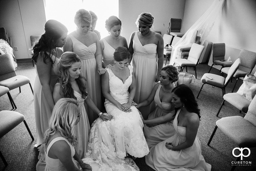 The bridesmaids praying with the bride.