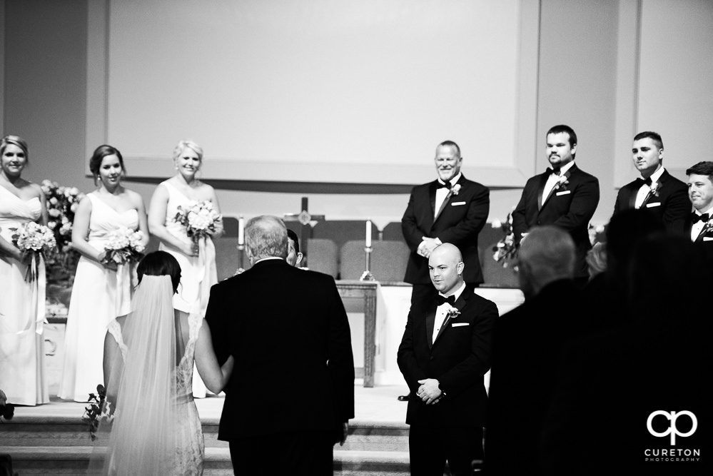 Bride and her father walking down the aisle with the groom's reaction.
