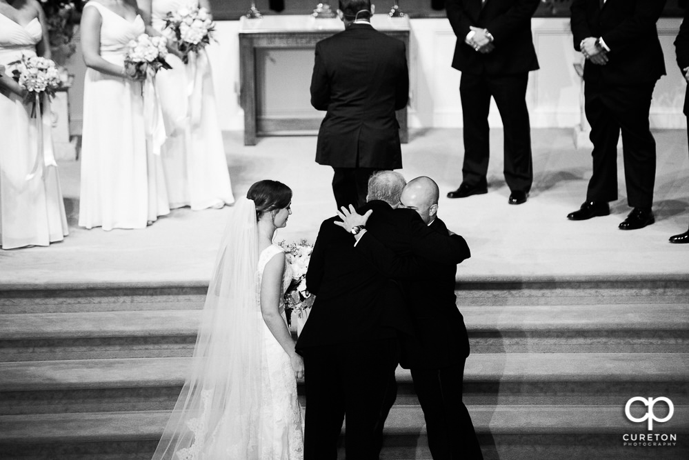 Bride's father hugging the groom.