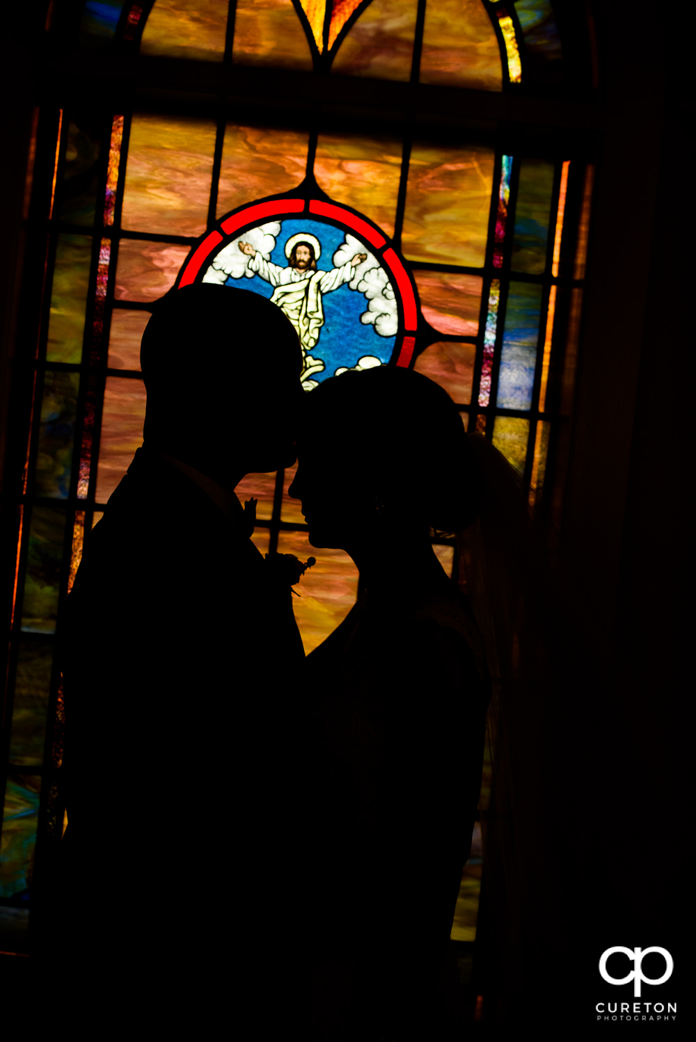 Silhouette of bride and groom in stained glass.