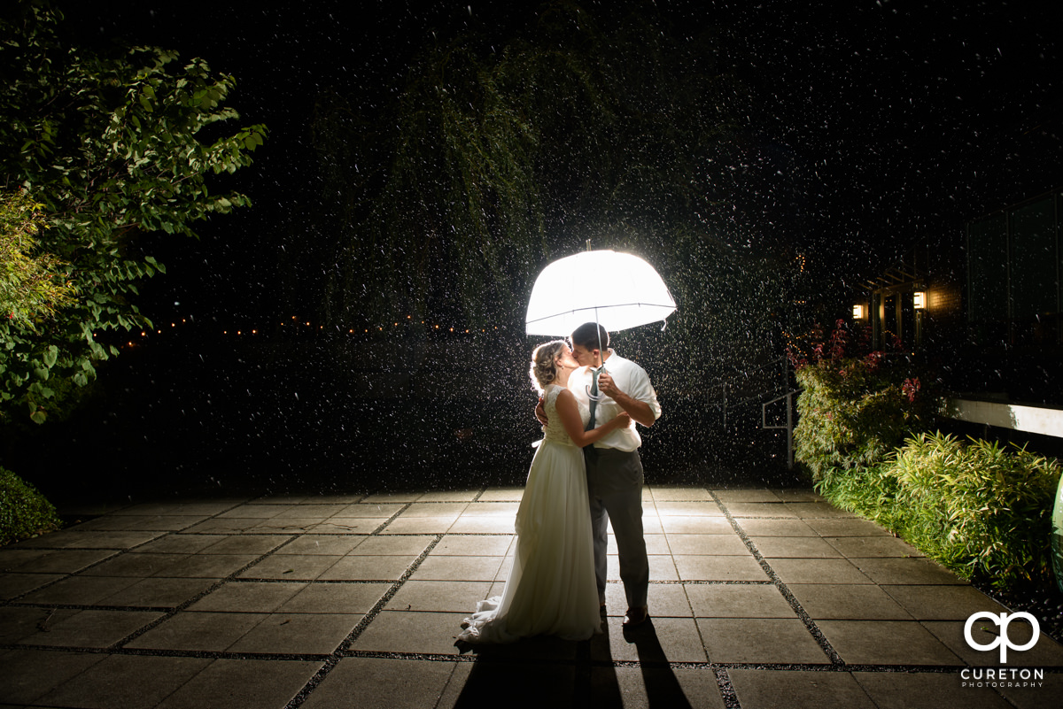 Bride and groom standing in the rain holding an umbrella in the courtyard at their wedding reception at Zen in Greenville,SC.