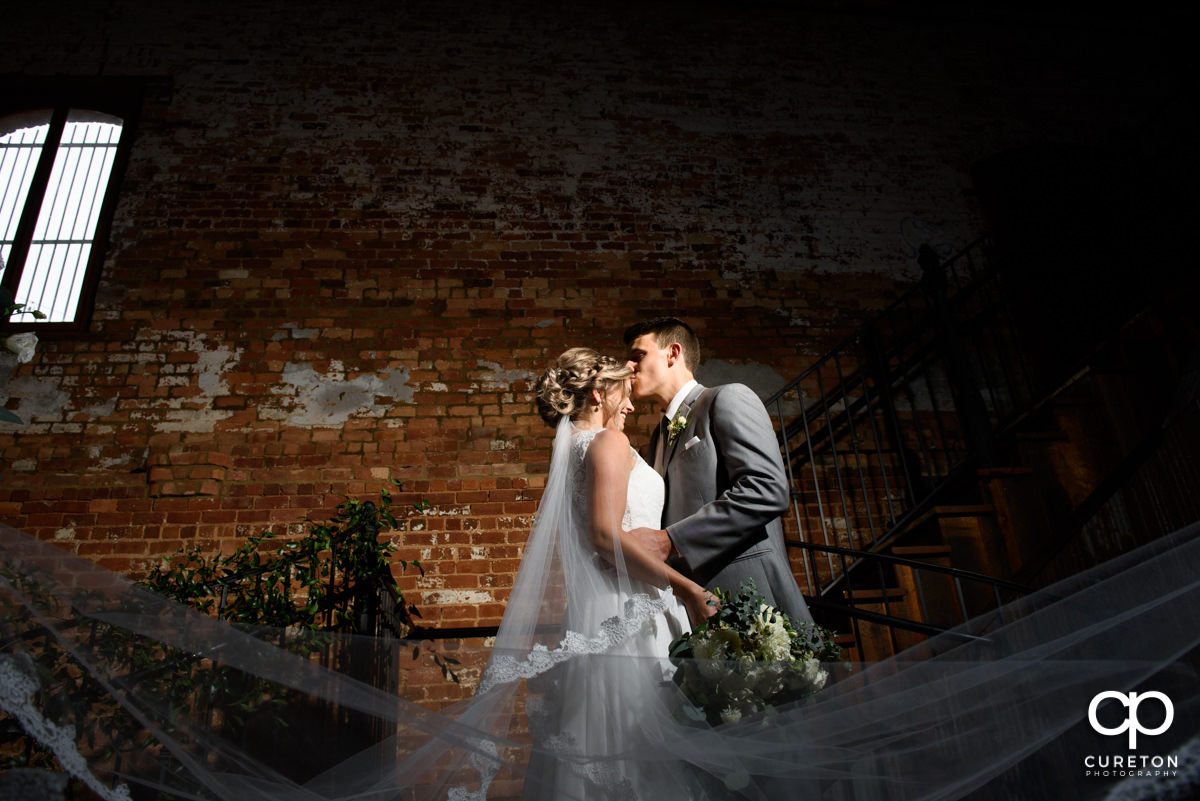Groom kissing his bride on the forehead on the steps as her veil blows inside the Old Cigar Warehouse before their wedding.