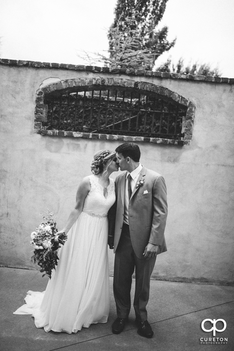 Black and white of a brode and groom kissing before their wedding at The Old Cigar Warehouse.