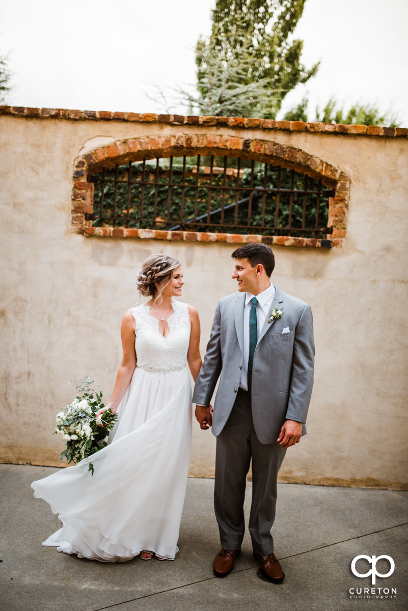 Bride and groom holding hands in the courtyard at Old Cigar Warehouse before their wedding in Greenville,SC.