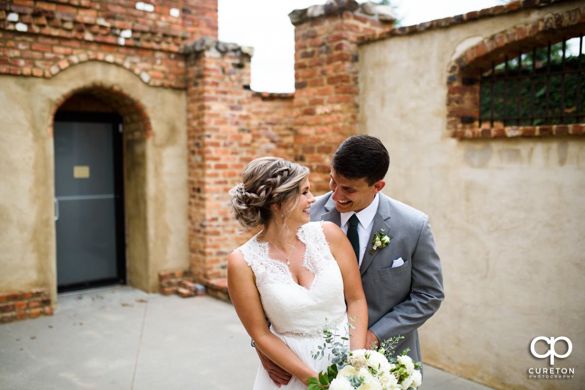 Bride and groom cuddling after a first look before their wedding ceremony at The Old Cigar Warehouse.