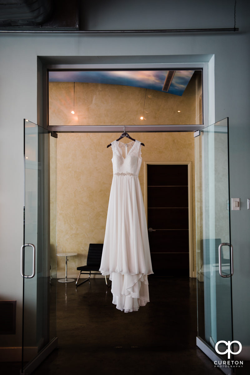 Bride's dress hanging in a doorway.