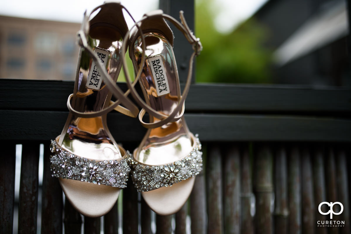 Bride's shoes on a bamboo fence.