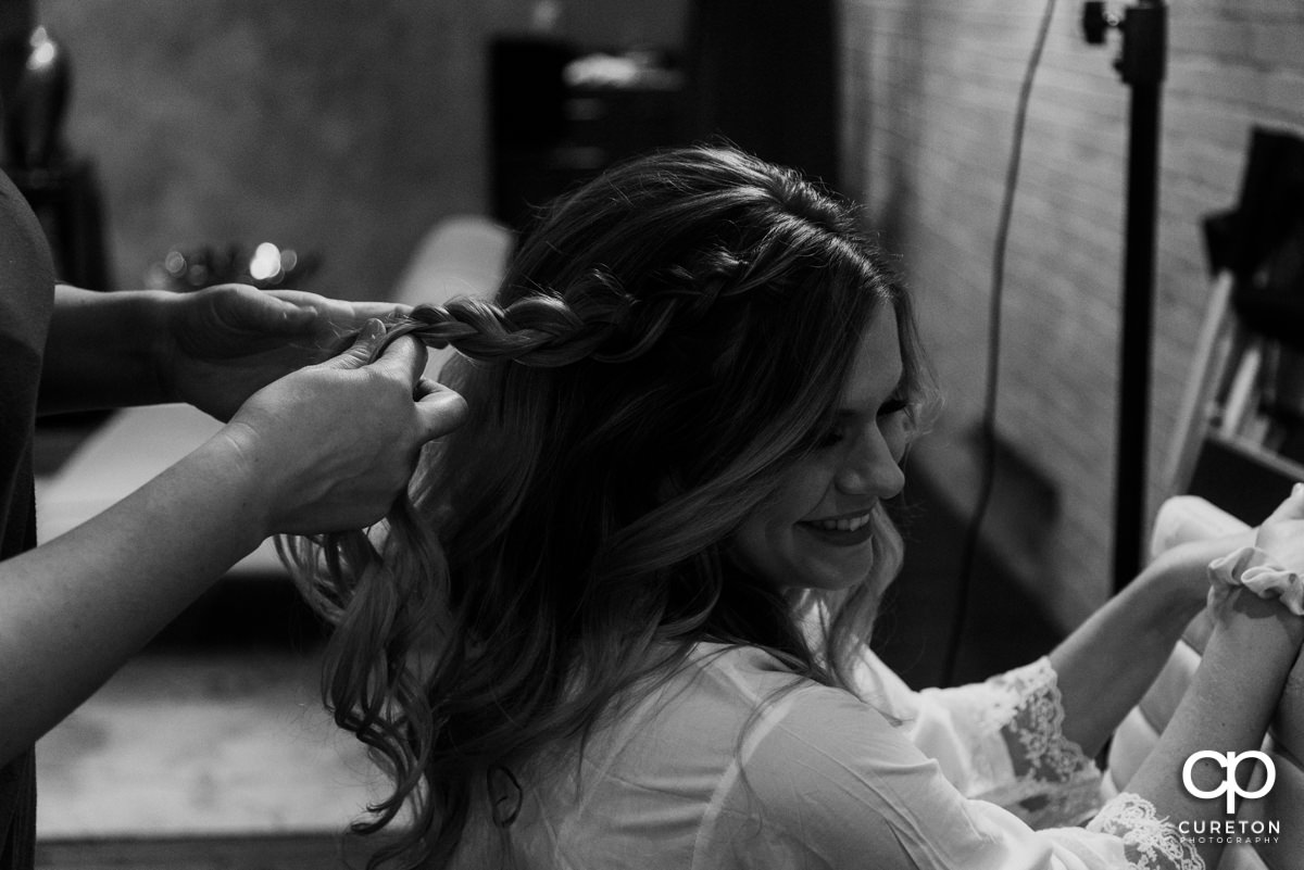 Bride smiling as her hair is braided before the wedding.