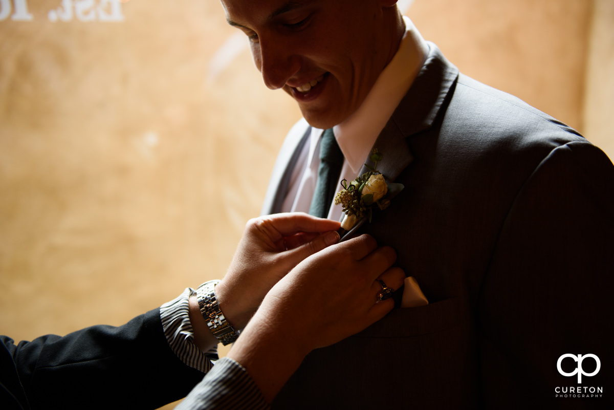 Groom having his boutonniere pinned.