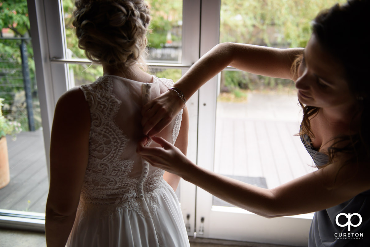 Bride having her dress buttoned.