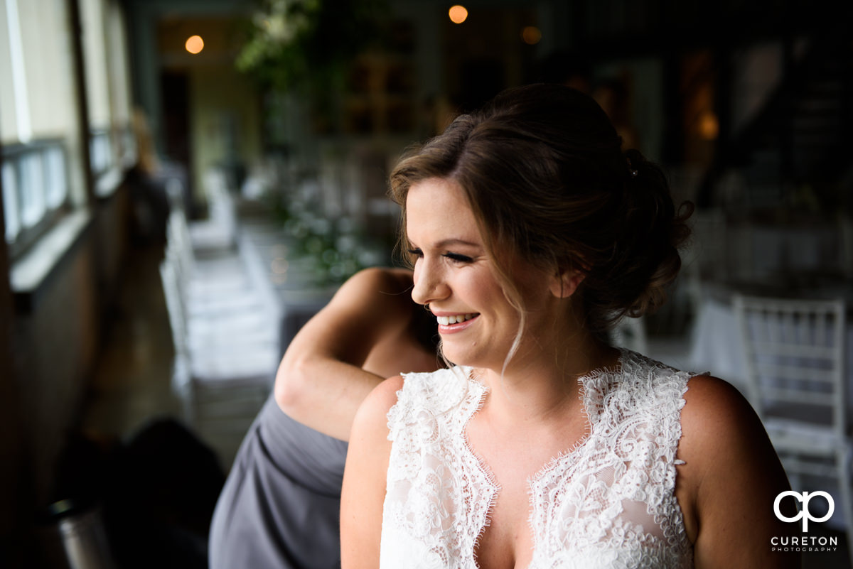 Bride smiling as her dress is buttoned.