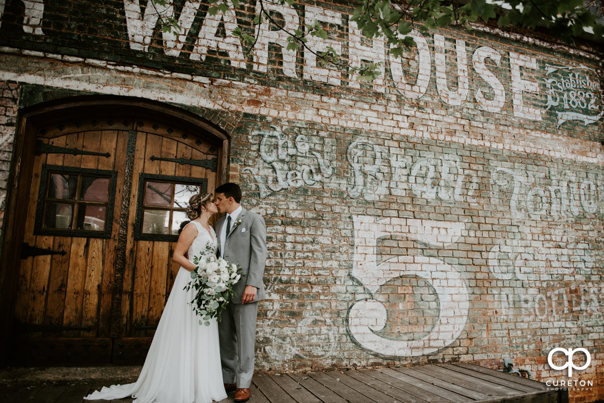 Bride and groom kissing outside of The Old Cigar Warehouse.