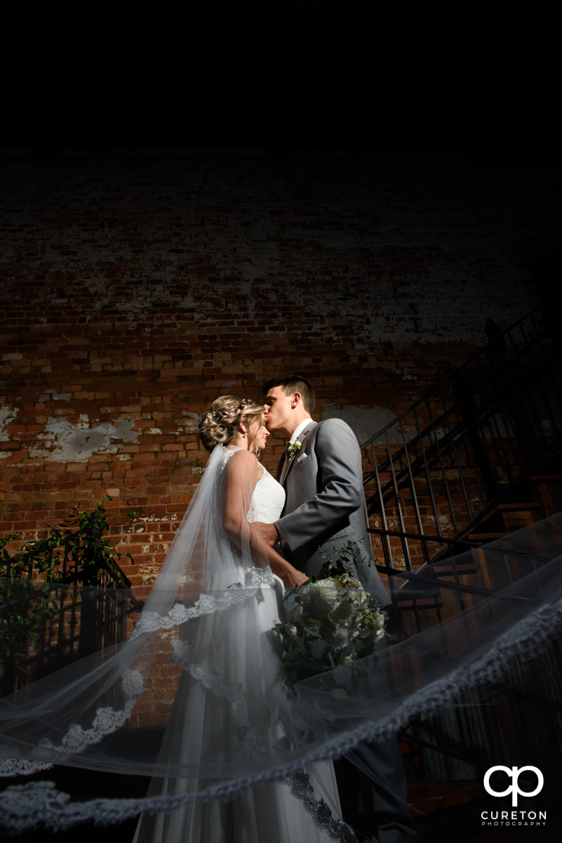 Bride and groom posing on the staircase with the veil blowing inside the Cigar Warehouse in Greenville,SC.