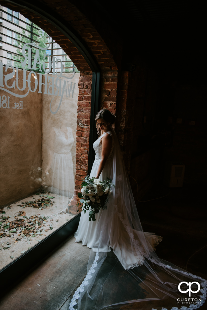 Bride standing in front of the window at The Old Cigar Warehouse looking at her amazing bouquet.