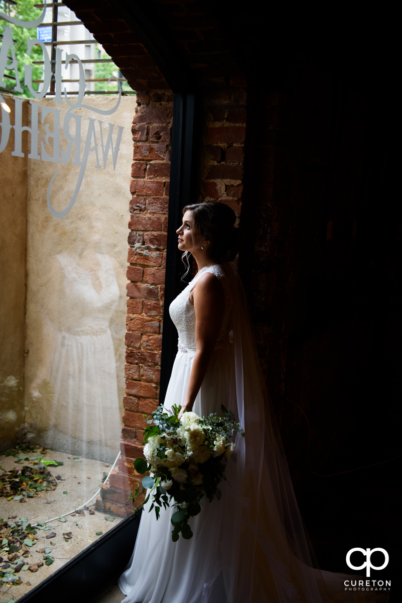 Bride looking out of the window at The Old Cigar Warehouse.