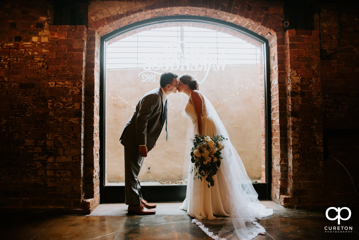 Bride and groom kissing in front of the huge window in the cellar at The Old Cigar Warehouse before their ceremony.