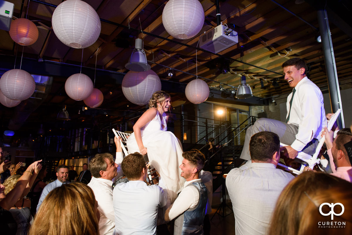Bride and groom on chairs during Hava Nagila at the Zen wedding reception.