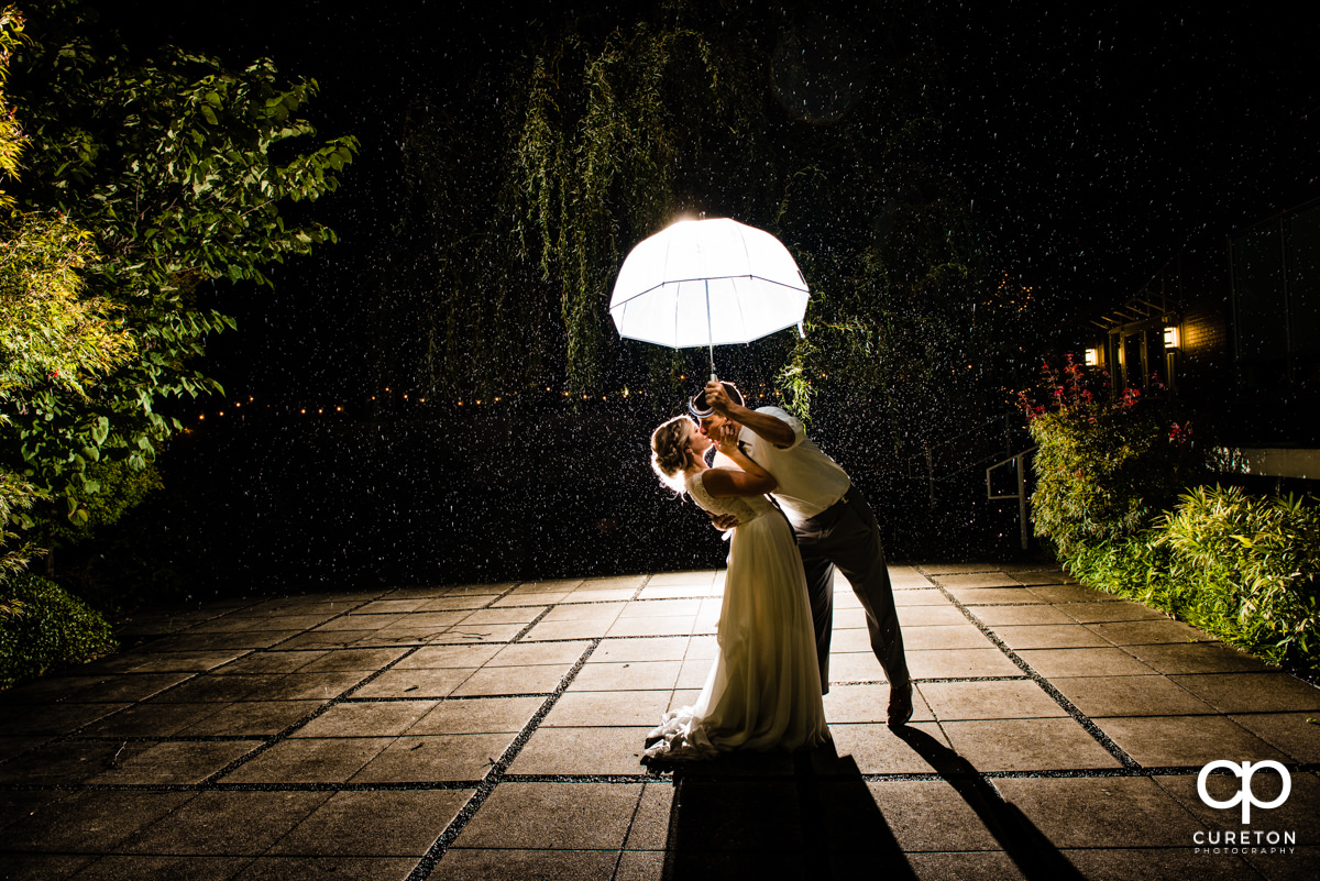 Bride and groom dancing in the rain at the wedding reception at Zen in downtown Greenville, SC.