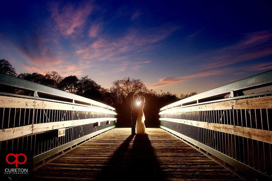 Couple on bridge with beautiful sunset after their wedding at Cleveland Park in Spartanburg,SC.