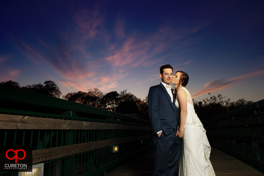 Bride kissing groom at sunset in downtown Spartanburg,SC.