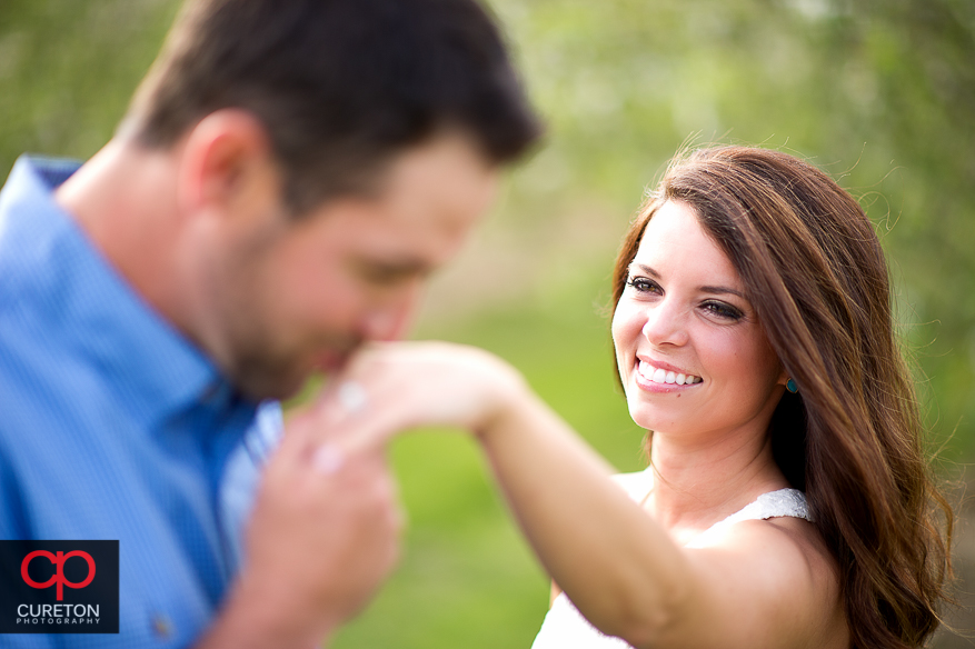 Groom kissing his bride to be's ring during their recent engagement session at an apple orchard in Hendersonville,NC.