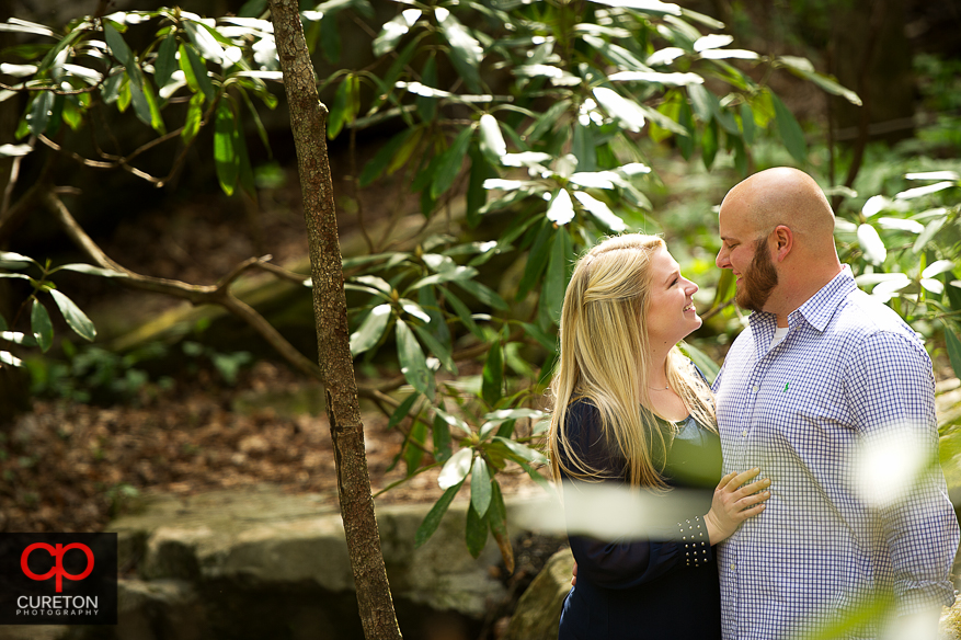 A couple liking at each other through the bushes.