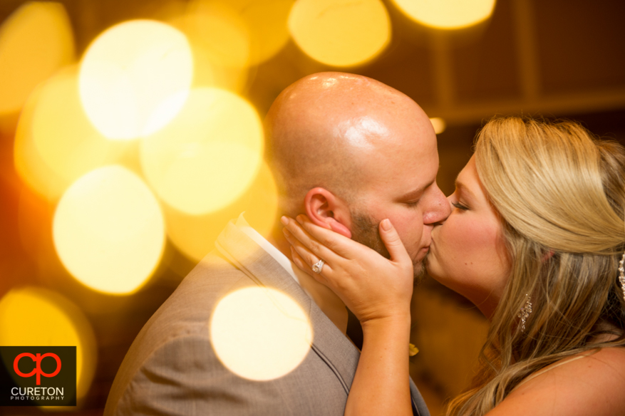 Married couple kissing after their Larkin's Sawmill wedding reception.