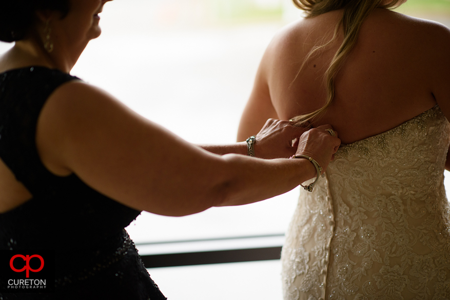 Bridesmiads help the bride into her dress.