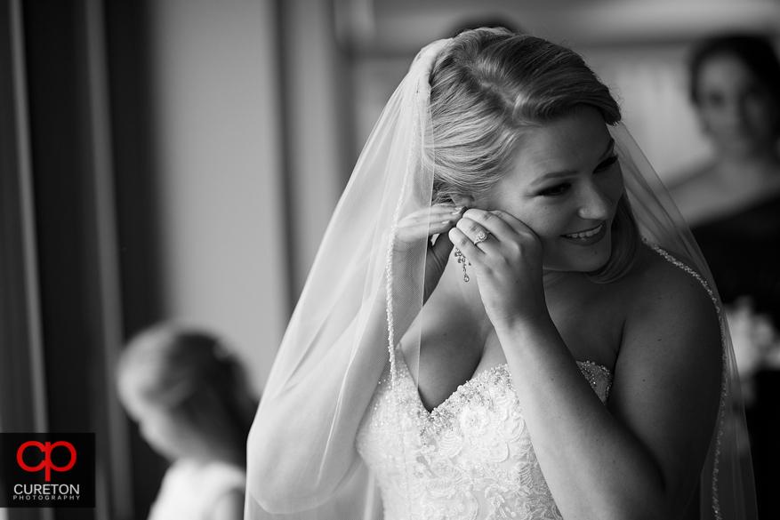 Bride standing in window light.