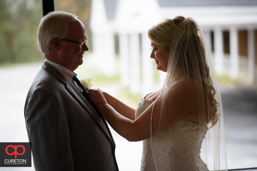 Bride helps her father pin flower.