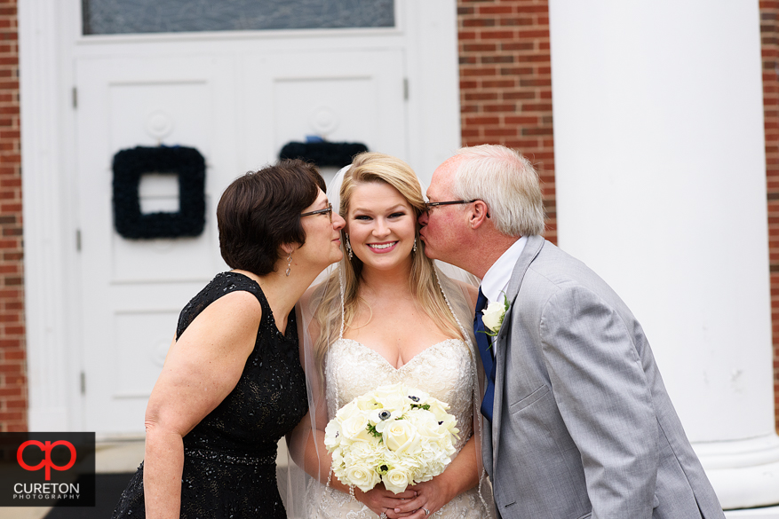 Bride's parents kiss her on the cheek.