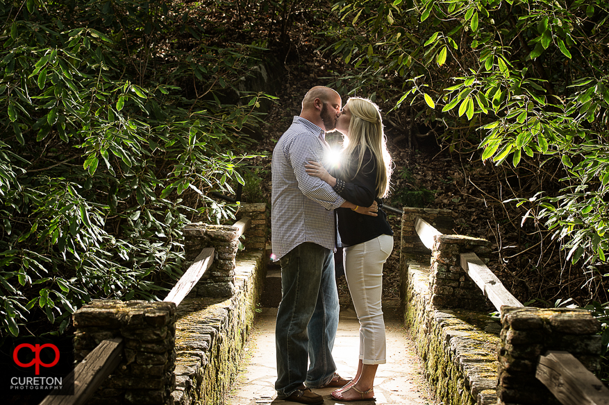 A couple kissing on the bridge during their Pearson's Falls engagement session.