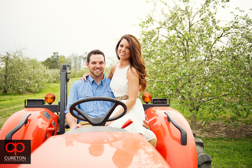 Couple sitting on a tractor during their recent engagement session at an apple orchard in Hendersonville,NC.