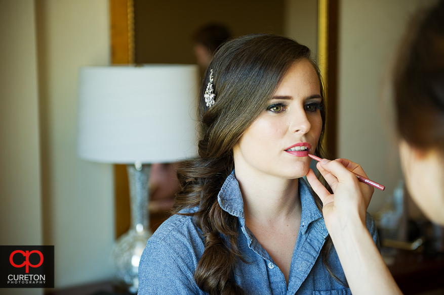 Bride getting her makeup touched up.