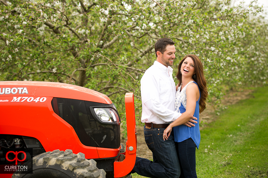 Bride to be laughing beside a tractor.