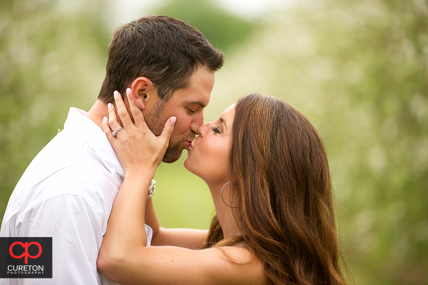 Girl kissing her fiancee during their recent engagement session at an apple orchard in Hendersonville,NC..