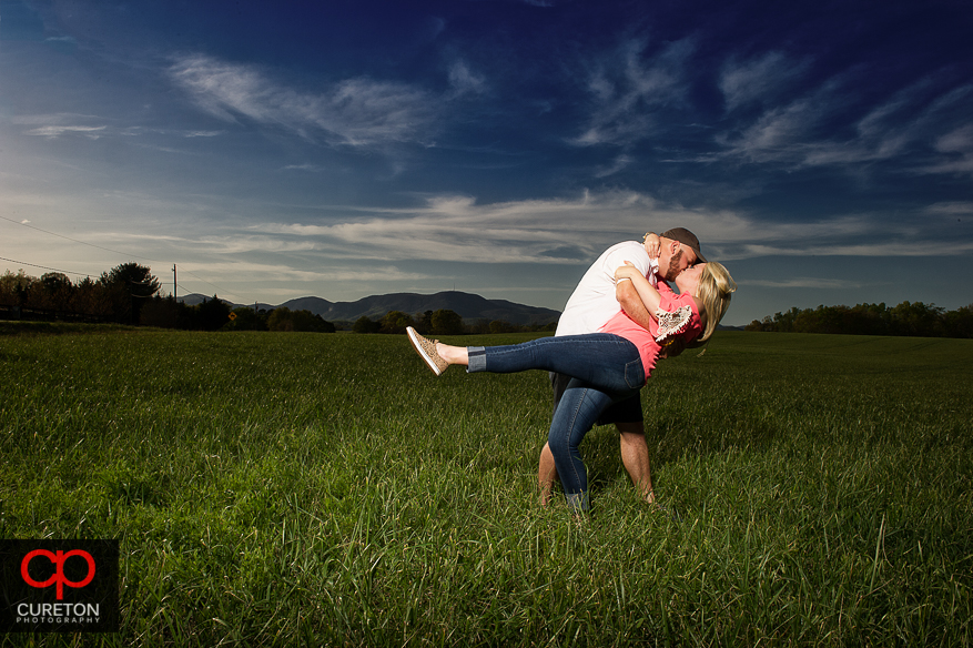 A couple dipping after their engagement session in a field.