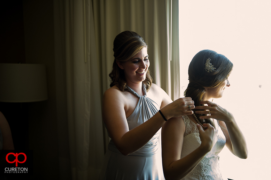 Bridesmaid helping bride with jewelry.