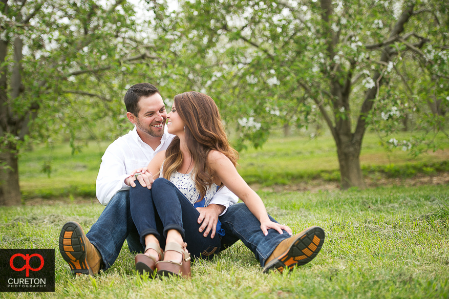 Couple sitting looking at each other during their recent engagement session at an apple orchard in Hendersonville,NC.