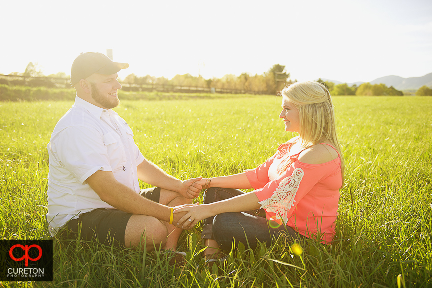 Couple sitting in a rural field during their engagement session.