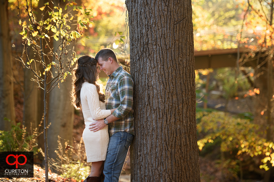 Engaged couple leaning on a tree in the park.