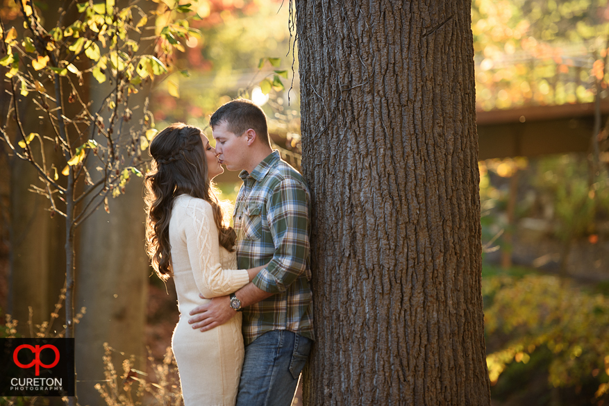 Couple kissing in downtown Greenville<SC during an engagement session.