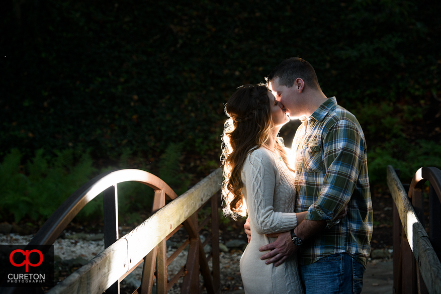 Backlit photo of a couple on the bridge at Falls Park.