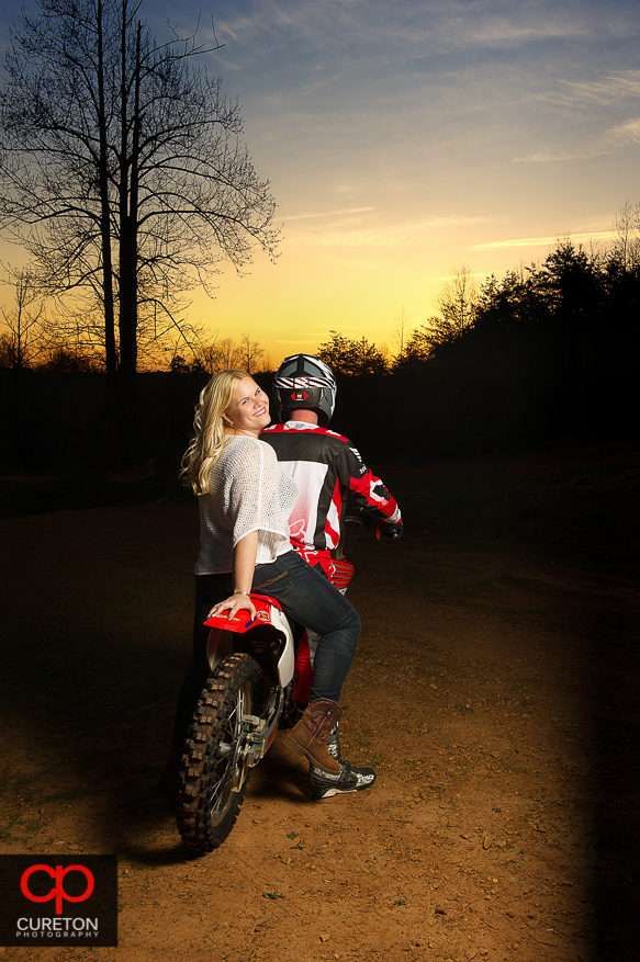 Bride to be on the back of a motorcycle at sunset during an engagement session in Greenville, SC.